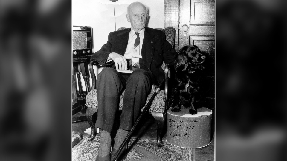 Former federal and provincial politician Alan Webster Neill sits with his dog in a photo from 1955 at the age of 87.(THE CANADIAN PRESS/HO-Alberni Valley Museum Photograph PN1247)