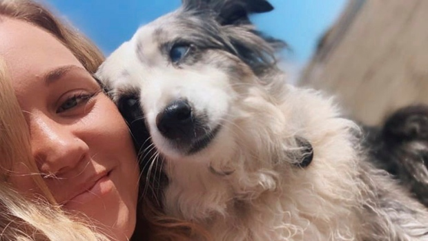 This undated selfie photo provided by Emilie Talermo showing Emilie Talermo and her dog Jackson taken in San Francisco, Calif. Talermo, is offering a US$7,000 reward for her blue-eyed miniature Australian Shepherd stolen from outside a grocery store. (Emilie Talermo via AP)