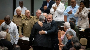 Cuban Prime Minister Manuel Marrero Cruz embraces Cuba's President Miguel Diaz-Canel during the closing session at the National Assembly of Popular Power in Havana, Cuba, Saturday, Dec. 21, 2019. Diaz-Canel named the former Tourism Marrero Cruz as the country's first prime minister since 1976. (AP Photo/Ramon Espinosa)