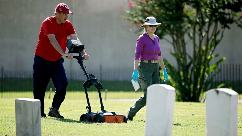 In this Monday, Oct. 7, 2019 photo, Scott Hammerstedt, with the Oklahoma Archeological Survey, and Angela Berg, with the Oklahoma State Medical Examiner's Office, use ground penetrating equipment to search for possible mass burial graves from Tulsa's 1921 Race Massacre at Oaklawn Cemetery in Okla. (Mike Simons/Tulsa World via AP)