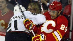 FILE - In this April 7, 2012, file photo, Anaheim Ducks' Sheldon Brookbank, left, checks Calgary Flames' Akim Aliu, a Nigerian-born Canadian, during third period NHL hockey action in Calgary, Alberta. (AP Photo/The Canadian Press, Jeff McIntosh, File)