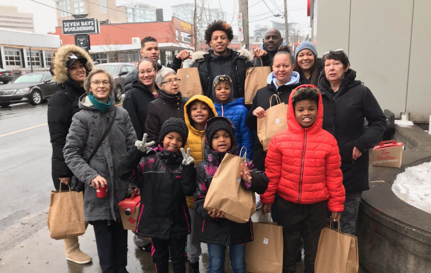 Halifax basketball star Lindell Wigginton (back-centre) and his family spent Sunday afternoon giving back to those in need on the streets of his hometown.