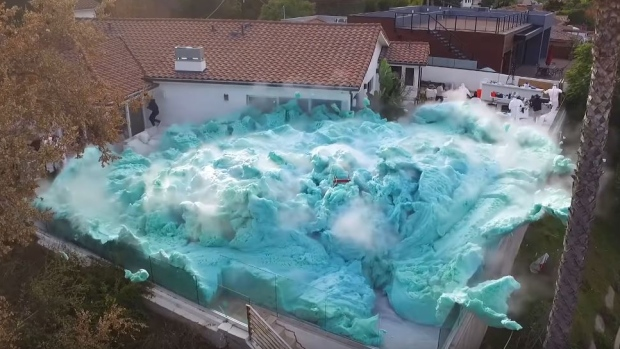 A group of YouTubers created a large-scale replica of a high school science experiment and staged a blue foam volcano eruption which covers an entire house balcony. (Nick Uhas/YouTube)