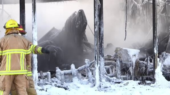 Firefighters stand in front of burned out building