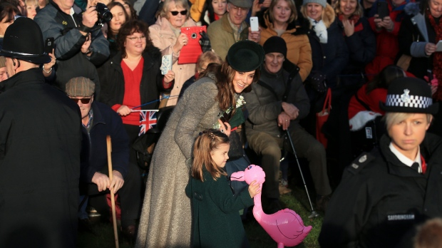 Britain's Catherine, Duchess of Cambridge, center left, speaks with her daughter Princess Charlotte as she holds a pink flamingo while greeting the public outside the St Mary Magdalene Church in Sandringham in Norfolk, England, Wednesday, Dec. 25, 2019. (AP Photo/Jon Super)