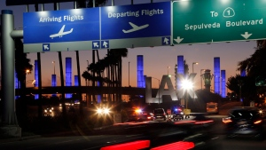In this Nov. 2, 2013 file photo lighted pylons line the entrance to Los Angeles International Airport in Los Angeles. (AP Photo/Reed Saxon,File)