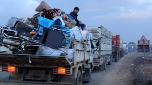 In this file photo, a man rides in a truck as civilians flee a Syrian military offensive in Idlib province on the main road near Hazano, Syria, Tuesday, Dec. 24, 2019. (AP Photo/Ghaith al-Sayed)