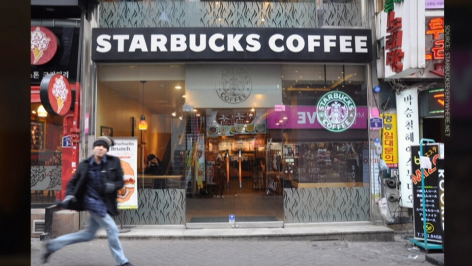 Starbucks guy Winter is pictured in front of a location in South Korea.