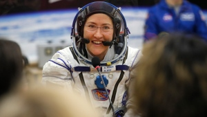 In this Thursday, March 14, 2019 file photo, U.S. astronaut Christina Koch, member of the main crew of the expedition to the International Space Station (ISS), speaks with her relatives through a safety glass prior the launch of Soyuz MS-12 space ship at the Russian leased Baikonur cosmodrome, Kazakhstan. (AP Photo/Dmitri Lovetsky, Pool)