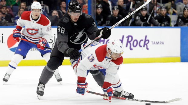 Tampa Bay Lightning defenseman Mikhail Sergachev (98) knocks down Montreal Canadiens center Max Domi (13) during the first period of an NHL hockey game Saturday, Dec. 28, 2019, in Tampa, Fla. (AP Photo/Chris O'Meara)