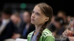 In this Wednesday, Dec. 11, 2019, file photo, Swedish climate activist Greta Thunberg listens to speeches before addressing the U.N. climate conference n Madrid, Spain. (AP Photo/Paul White)