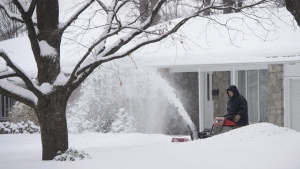 A person uses a snowblower to clear their driveway as a major storm hits Ottawa and the National Capital area on Jan. 8, 2018. (Sean Kilpatrick / THE CANADIAN PRESS)