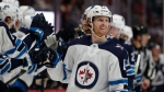 Winnipeg Jets left wing Kyle Connor is congratulated as he passes the team box after scoring a goal against the Colorado Avalanche during the third period of an NHL hockey game Tuesday, Dec. 31, 2019, in Denver. Winnipeg won 7-4. (AP Photo/David Zalubowski)