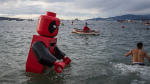 People participate in the 100th anniversary Polar Bear Swim at English Bay, in Vancouver, Wednesday, Jan. 1, 2020. According to the city, the initial swim was in 1920, when approximately 10 swimmers participated. (Darryl Dyck / THE CANADIAN PRESS)