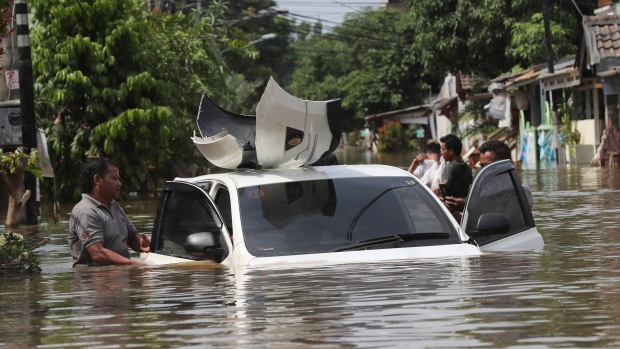 A resident inspects a car flooded neighbourhood in Tanggerang outside Jakarta, Indonesia, Thursday, Jan. 2, 2020. (AP Photo/Tatan Syuflana)