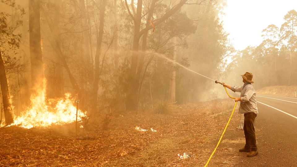 A man uses a water hose to battle a fire near Moruya, Australia, Saturday, Jan. 4, 2020. (AP Photo/Rick Rycroft)