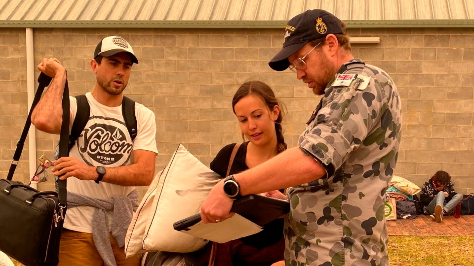 In this photo released and taken Jan. 2, 2020, by the Australian Department of Defense, Chief Petty Officer Maritime Logistics - Personnel Heath Jones checks names of evacuees at the registration point, in Mallacoota, Victoria Australia. (Australian Department of Defense via AP)
