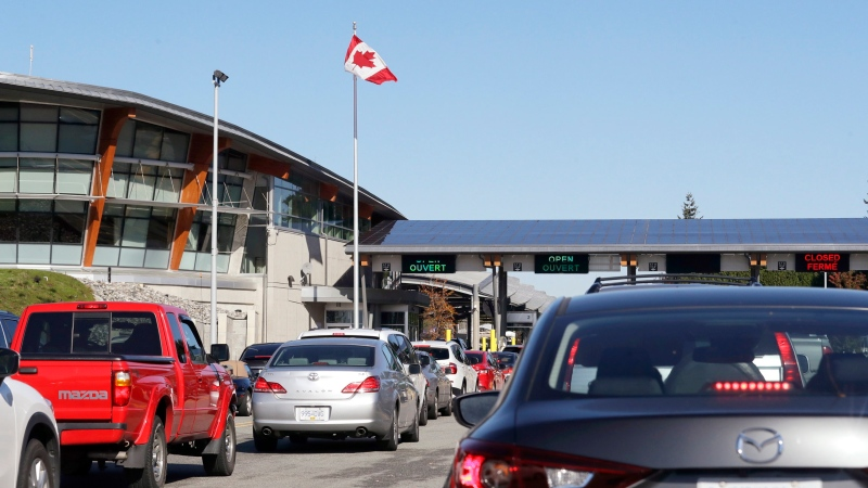 In this Oct. 9, 2019 photo, traffic enters Canada from the United States at the Peace Arch Border Crossing, in Blaine, Wash. (AP Photo/Elaine Thompson)