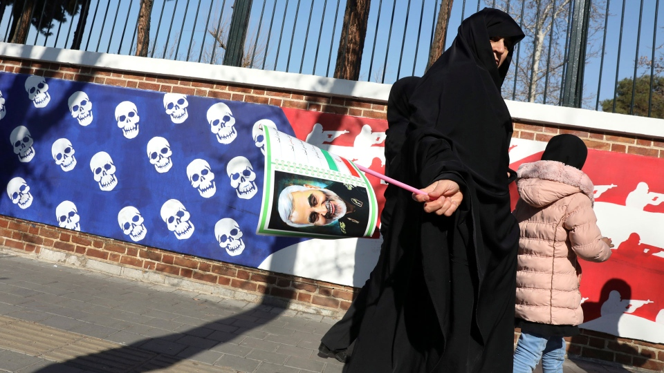 A mourner holds a poster of Iranian Gen. Qassem Soleimani, as she walks back from a funeral ceremony for him and his comrades, who were killed in Iraq in a U.S. drone attack on Friday, passing a satirical drawing of the U.S. flag painted on the wall of the former U.S. Embassy in Tehran, Iran, Monday, Jan. 6, 2020. (AP Photo/Vahid Salemi)