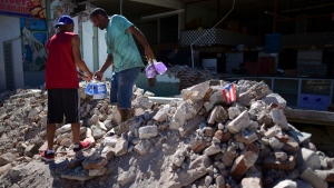 Store owners and family help remove supplies from Ely Mer Mar hardware store, which partially collapsed after an earthquake struck Guanica, Puerto Rico, Tuesday, Jan. 7, 2020. (AP Photo/Carlos Giusti)