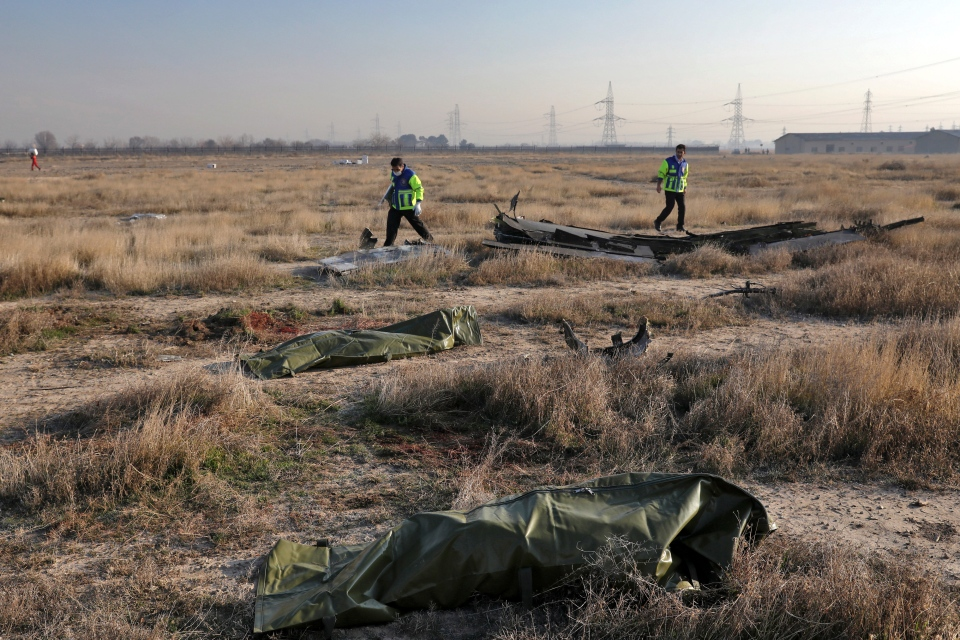 Rescue workers search the scene where a Ukrainian plane crashed as the bodies of victims in body bags lie on the ground, in Shahedshahr, southwest of the capital Tehran, Iran, Wednesday, Jan. 8, 2020. (AP Photo/Ebrahim Noroozi)