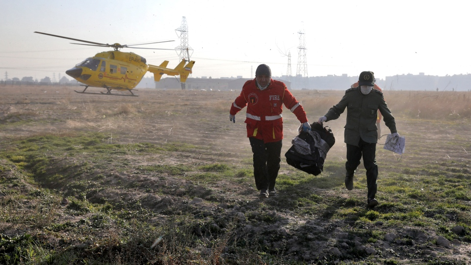 Rescue workers carry items retrieved from the scene where a Ukrainian plane crashed in Shahedshahr, southwest of the capital Tehran, Iran, Wednesday, Jan. 8, 2020. (AP Photo/Ebrahim Noroozi)