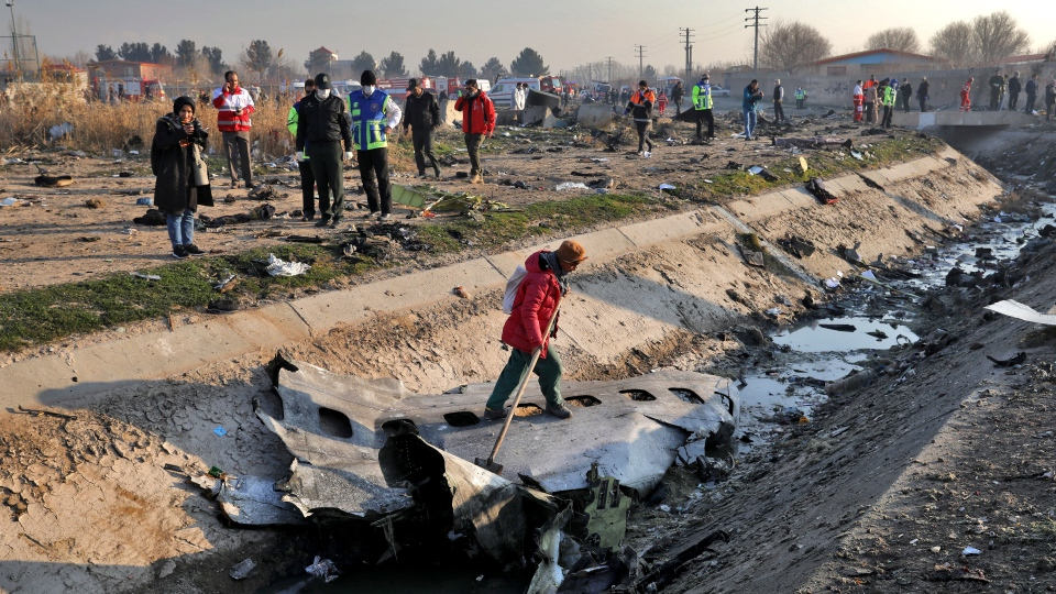 Rescue workers inspect the scene where a Ukrainian plane crashed in Shahedshahr, southwest of the capital Tehran, Iran, Wednesday, Jan. 8, 2020. (AP Photo/Ebrahim Noroozi)