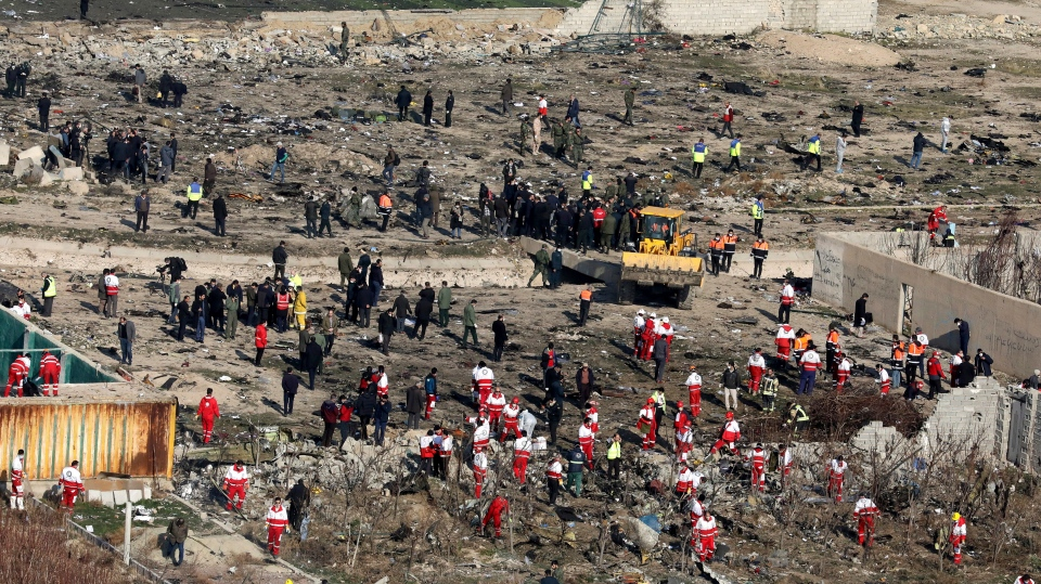 Rescue workers search the scene where an Ukrainian plane crashed in Shahedshahr, southwest of the capital Tehran, Iran, Wednesday, Jan. 8, 2020. (AP Photo/Ebrahim Noroozi)