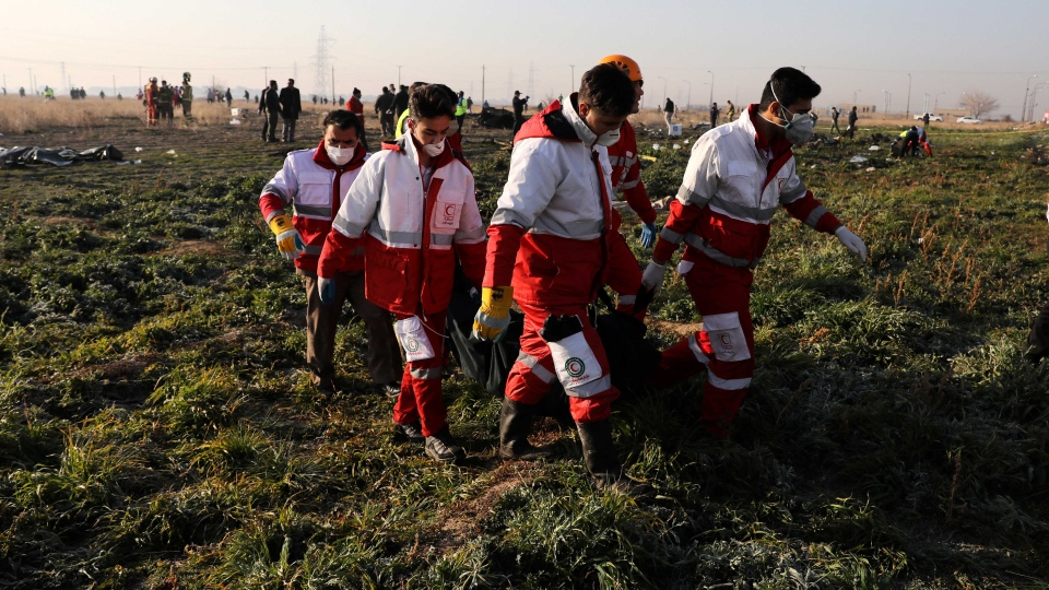 Rescue workers carry the body of a victim of an Ukrainian plane crash in Shahedshahr southwest of the capital Tehran, Iran, Wednesday, Jan. 8, 2020. (AP Photo/Ebrahim Noroozi)