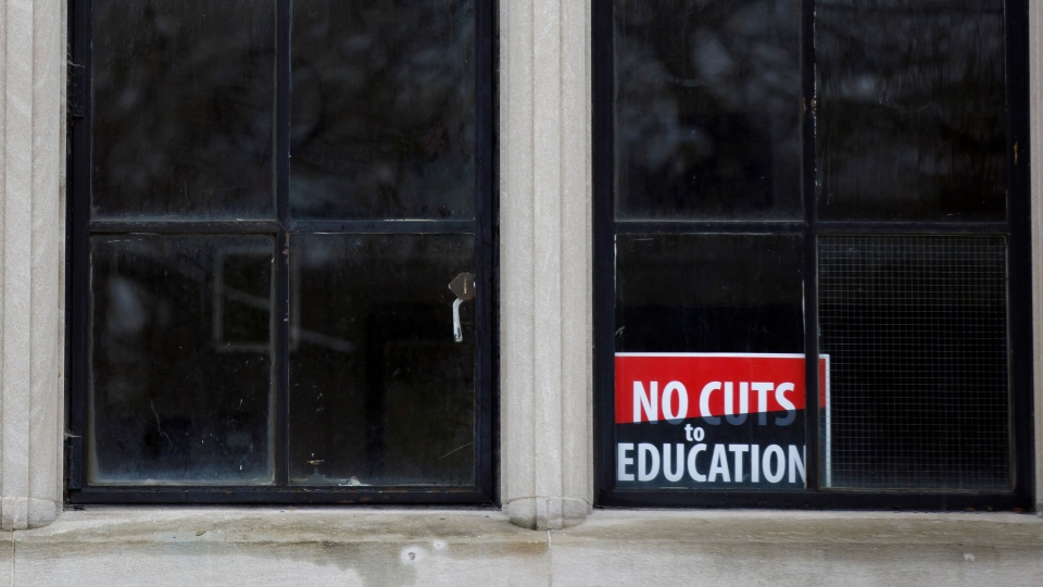A sign is seen inside a secondary school classroom window as teachers walk the picket line outside in Toronto, Wednesday, Dec. 4, 2019. THE CANADIAN PRESS/Cole Burston
