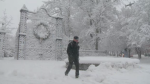 A pedestrian walks past the snow-covered entrance to the Public Gardens in Halifax during a storm on Jan. 8, 2020.