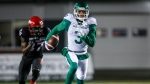 Saskatchewan Roughriders' Nick Marshall, right, runs an interception as Calgary Stampeders' Richie Sindani chases him during first half CFL football action in Calgary, Friday, Oct. 11, 2019.THE CANADIAN PRESS/Jeff McIntosh
