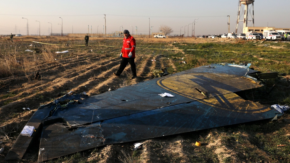 A rescue worker searches the scene where a Ukrainian plane crashed in Shahedshahr southwest of the capital Tehran, Iran, Wednesday, Jan. 8, 2020. (AP Photo/Ebrahim Noroozi)