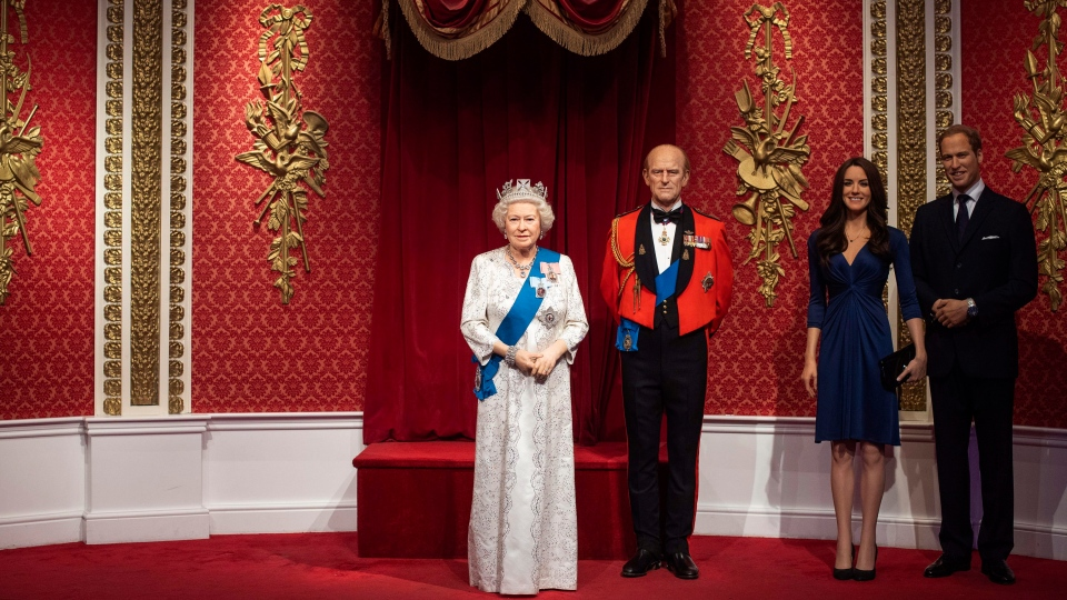 The empty space after the figures of Britain's Prince Harry and Meghan, Duchess of Sussex, left, were removed next to Queen Elizabeth II, Prince Philip and Prince William and Kate, Duchess of Cambridge, at Madame Tussauds in London, Thursday Jan. 9, 2020. (Victoria Jones/PA via AP