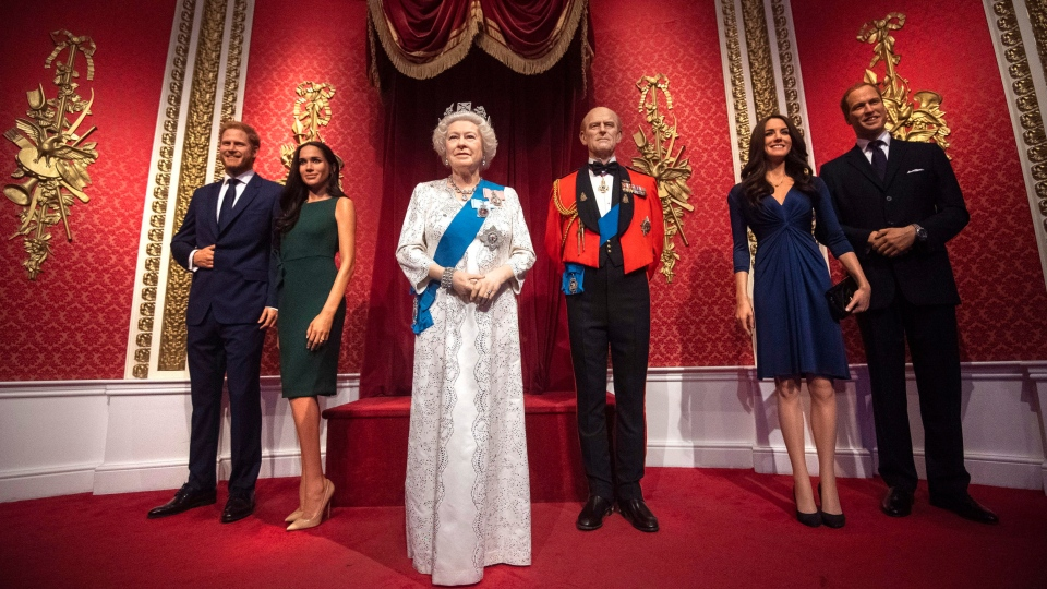 The figures of Britain's Prince Harry and Meghan, Duchess of Sussex, left, in their original positions next to Queen Elizabeth II, Prince Philip and Prince William and Kate, Duchess of Cambridge, at Madame Tussauds in London, Thursday Jan. 9, 2020. (Victoria Jones/PA via AP)