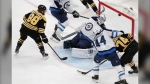 Boston Bruins right wing David Pastrnak (88) scores against Winnipeg Jets goaltender Laurent Brossoit (30) during the third period of an NHL hockey game Thursday, Jan. 9, 2020, in Boston. It was his third goal of the game. (AP Photo/Elise Amendola)