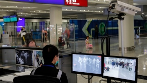 FILE - In this Jan. 4, 2020, file photo, a health surveillance officer monitors passengers arriving at the Hong Kong International airport in Hong Kong. A preliminary investigation into viral pneumonia illnesses sickening dozens of people in and around China has identified the possible cause as a new type of coronavirus, state media said Thursday, Jan. 9, 2020. (AP Photo/Andy Wong, File)