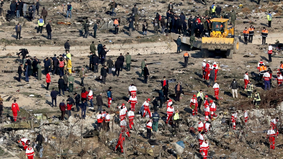In this Wednesday, Jan. 8, 2020, photo, rescue workers search the scene where a Ukrainian plane crashed in Shahedshahr, southwest of the capital Tehran, Iran. (AP Photo/Ebrahim Noroozi)