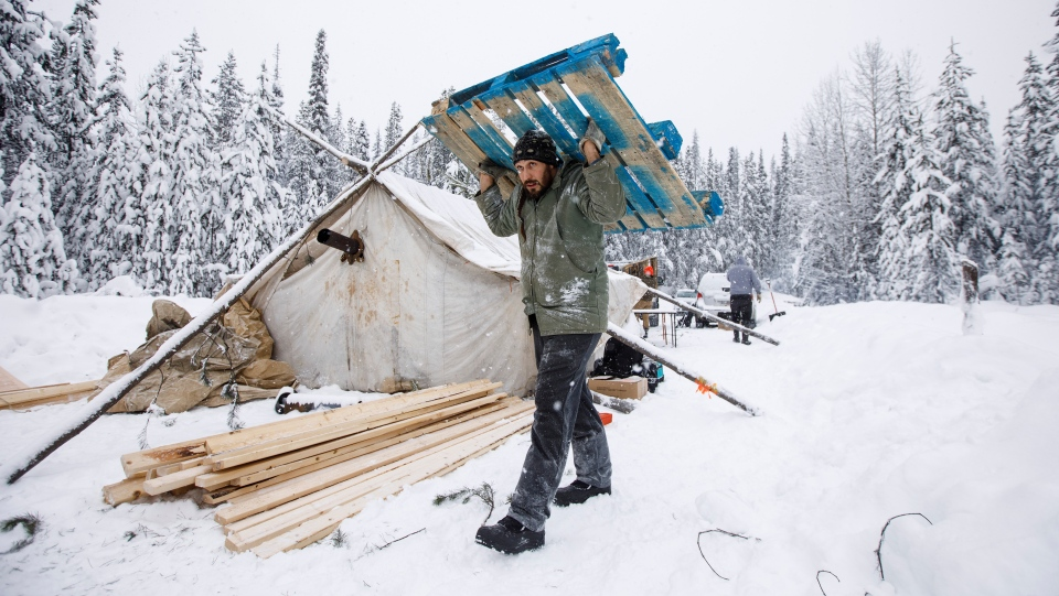 Cody Merriman a supporter of the Wet'suwet'en Hereditary Chiefsand who opposes the Costal Gaslink pipeline carries a pallet for flooring at the support station at kilometre 39 near the Gidimt'en checkpoint near Houston B.C., on Thursday January 8, 2020. THE CANADIAN PRESS/Jason Franson
