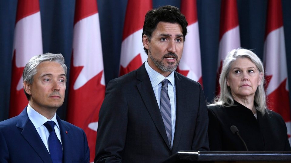 Prime Minister Justin Trudeau stands with Minister of Foreign Affairs Francois-Philippe Champagne, left, and Deputy Minister of National Defence Jody Thomas, right, during a press conference at the National Press Theatre in Ottawa, on Saturday, Jan. 11, 2020. THE CANADIAN PRESS/Justin Tang