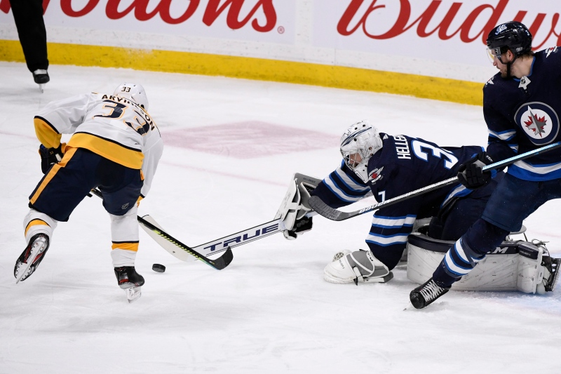 Winnipeg Jets goaltender Connor Hellebuyck (37) makes a save on Nashville Predators' Viktor Arvidsson (33) during first period NHL action in Winnipeg on Sunday Jan. 12, 2020. THE CANADIAN PRESS/Fred Greenslade