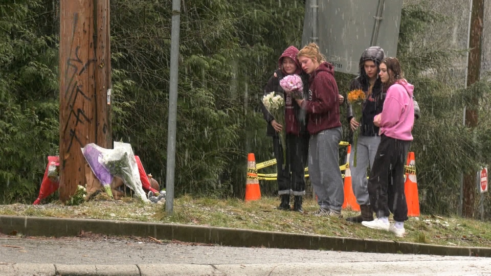 Kerri Houston and three friends brought bouquets of flowers Sunday to the growing memorial at the intersection where Elijah Drasyl's BMW struck a telephone pole. (CTV)