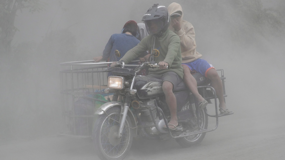 A family rides their motorcycle through clouds of ash as they evacuate to safer grounds as Taal Volano continues to erupt near Lemery, Batangas, southern Philippines on Monday, Jan. 13, 2020. (AP Photo/Aaron Favila)