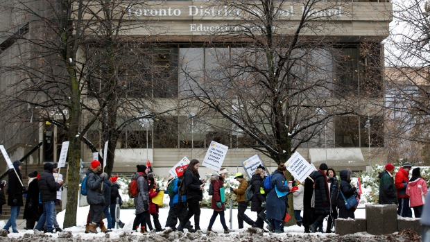 Striking teachers of the Ontario Secondary School Teachers Federation picket outside of the Toronto District School Board head office on Yonge St. in Toronto, Wednesday, Dec. 4, 2019. (THE CANADIAN PRESS/Cole Burston)