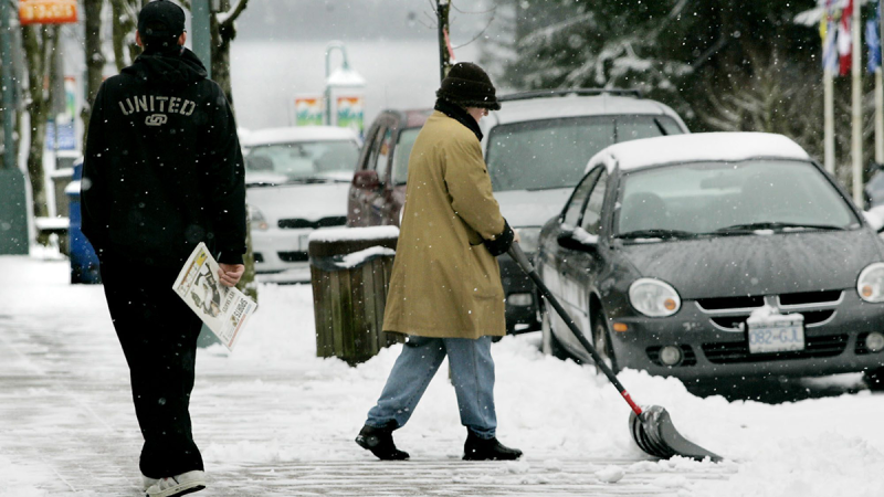 A man strolls past a women shovelling the sidewalk in North Vancouver following a snowstorm. (Chuck Stoody / The Canadian Press)