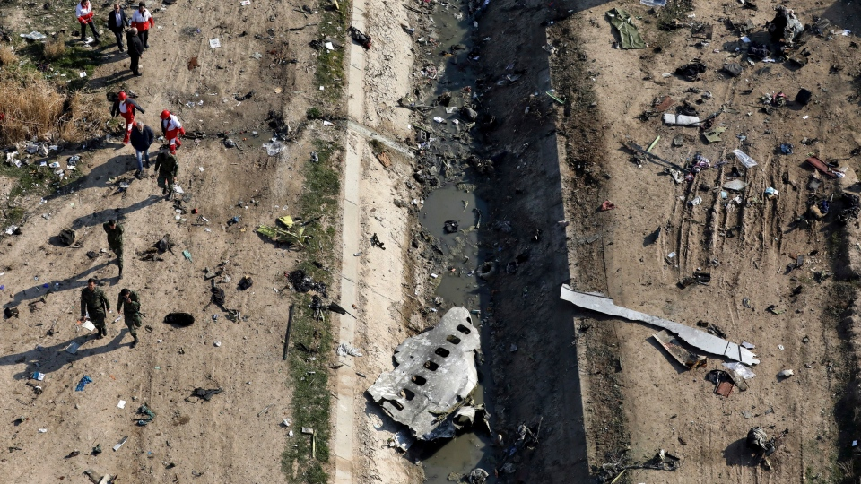 In this Wednesday, Jan. 8, 2020 photo, rescue workers search the scene where a Ukrainian plane crashed in Shahedshahr, southwest of the capital Tehran, Iran. (AP Photo/Ebrahim Noroozi)