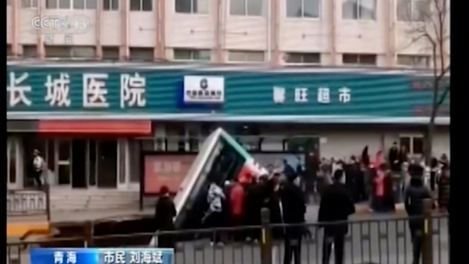 In this image made from CCTV video, a bus plunges into a sinkhole in the center of a downtown street, Monday, Feb. 13, 2020, in Xining, Qinghai province, China. (CCTV via AP)