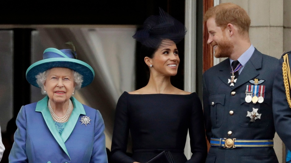 Queen Elizabeth II, and Meghan the Duchess of Sussex and Prince Harry watch a flypast of Royal Air Force aircraft pass over Buckingham Palace in London on Tuesday, July 10, 2018. THE CANADIAN PRESS/AP, Matt Dunham