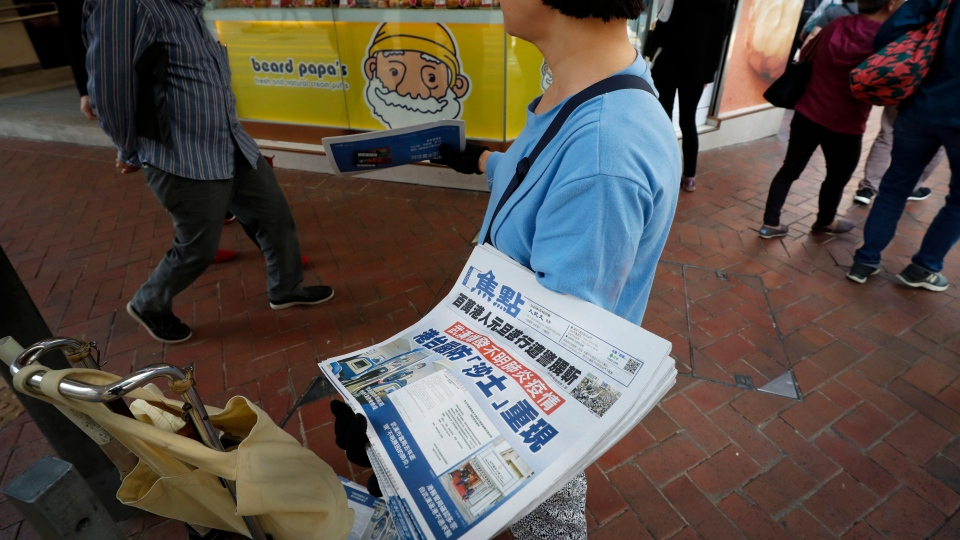 A vendor gives out copies of newspaper with a headlines of 'Wuhan break out a new type of coronavirus, Hong Kong prevent SARS repeat' at a street in Hong Kong, Saturday, Jan. 11, 2020. THE CANADIAN PRESS/AP-Andy Wong