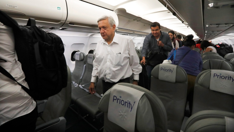 In this March 9, 2019 file photo, Mexican President Andres Manuel Lopez Obrador walks off the plane after traveling in economy class aboard a commercial flight from Guadalajara to Mexico City. Lopez Obrador said Friday that he will continue travelling to dedicate infrastructure projects around the country in spite of growing restrictions prompted by the coronavirus epidemic, including a shutdown of most federal government operations.